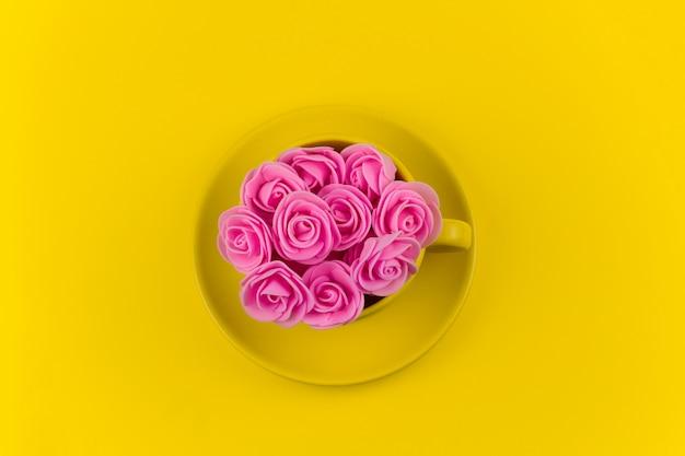 Draufsichtgelb-teebecher voll rosa blumen auf gelb