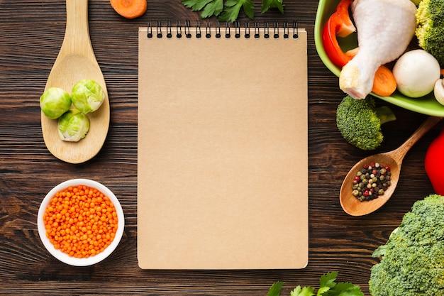 Draufsichtgemüsemischung und hühnertrommelstock in der schüssel mit leerem notizbuch