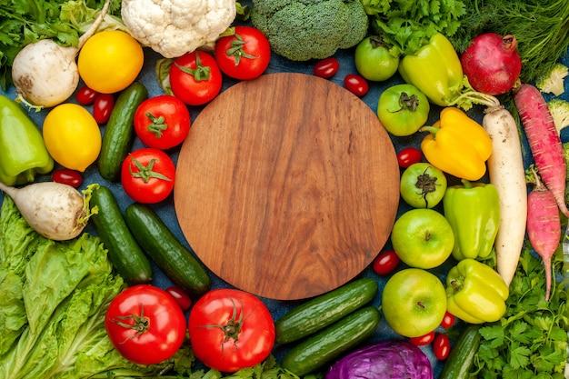 Draufsichtgemüsezusammensetzung mit frischen früchten auf blauem tischmahlzeitsalat gesundes leben reife farbdiät
