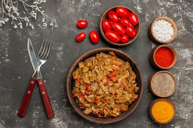 Draufsichtgewürze auf dem tisch vier schüsseln mit bunten gewürzen und tomaten neben dem teller mit grünen bohnen auf dem dunklen tisch