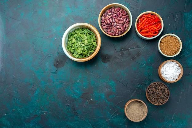 Draufsichtgewürze und bohnen mit grün auf dem dunkelblauen hintergrundpfeffergrün-produktfarbfoto