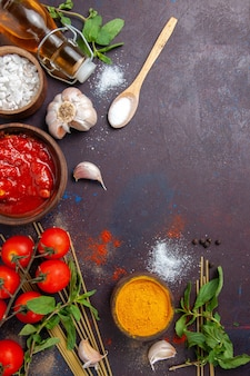 Draufsichtgewürze und soße mit tomaten auf dunkler hintergrundmahlzeit würzige warme lebensmittelfarbe