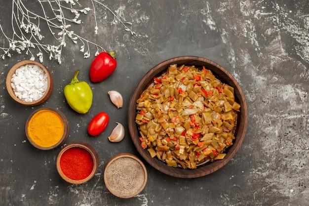 Draufsichtgewürze und teller mit grünen bohnen und bunten gewürzen der tomaten auf dem dunklen tisch