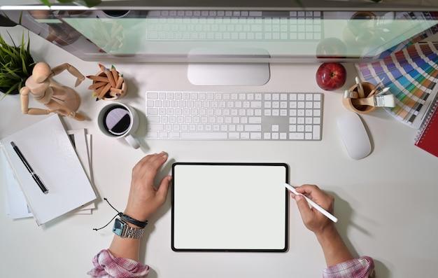 Draufsichtgrafikdesign, das mit zeichentablett und tischrechner am künstlerarbeitsplatz arbeitet
