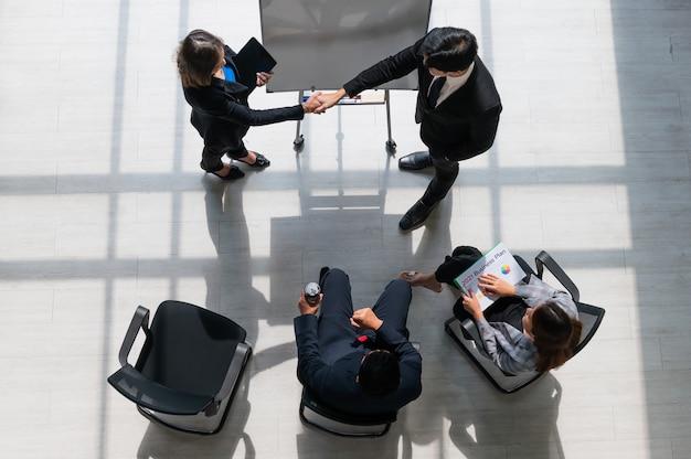 Draufsichtgruppe des geschäftsteammeetings im modernen büro