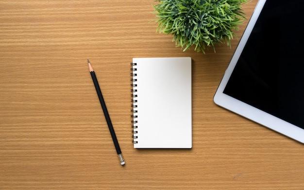 Draufsichtgruppe des stationären notizblocks, des bleistifts, der tablette und der anlage des büros am schreibtisch