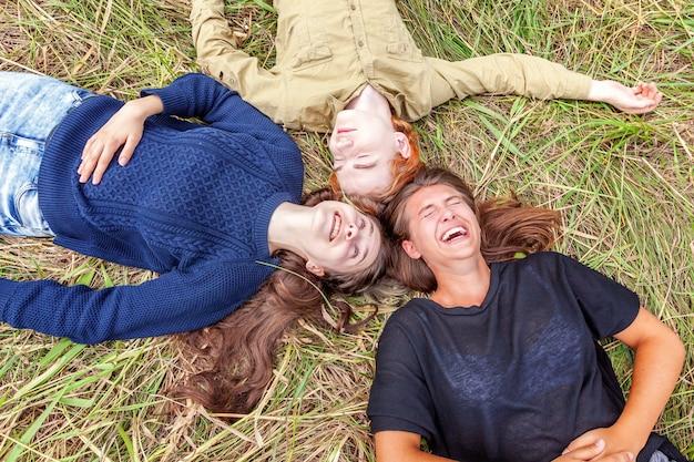 Draufsichtgruppe von drei freunden, die auf gras im kreis liegen lächelnd und spaß haben
