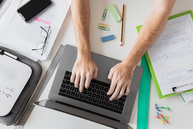 Draufsichthände, die an dem laptop umgeben durch briefpapierelemente arbeiten