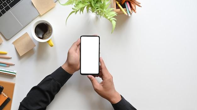 Draufsichthände, die ein weißes leeres bildschirm-smartphone über kaffeetasse, topfpflanze, stiften, computer-laptop, notizbuch und lineal halten, die auf weißem schreibtisch zusammenstellen.