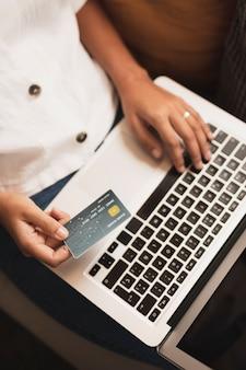 Draufsichthände, die eine kreditkarte und einen laptop halten