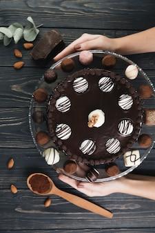 Draufsichthände, die schokoladenkuchen halten