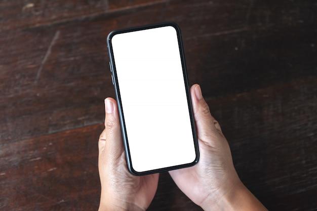 Draufsichthände, die schwarzes mobiltelefon mit leerem desktop-bildschirm auf hölzernem tischhintergrund halten