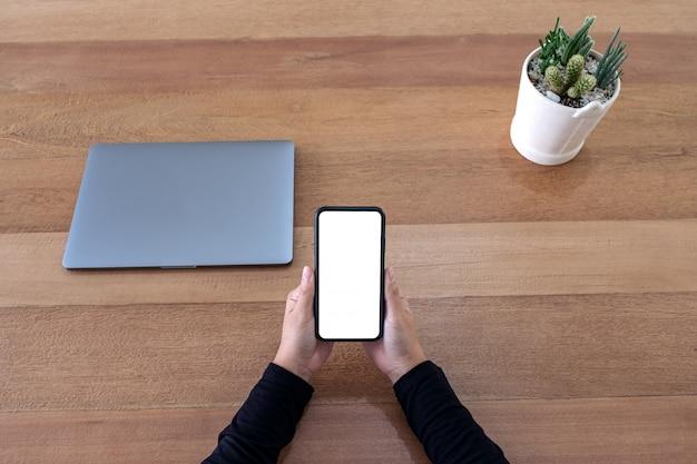 Draufsichthände, die schwarzes mobiltelefon mit leerem desktop-bildschirm mit laptop und kaktustopf auf hölzernem tischhintergrund halten