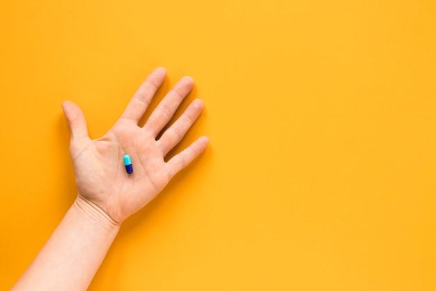 Draufsichthand, die eine pille mit kopienraum hält