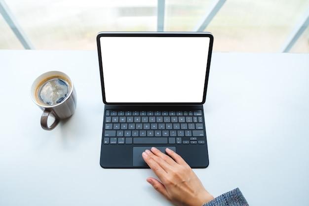 Draufsichthand, die tablet-touchpad mit leerem weißen desktop-bildschirm als computer-pc, kaffeetasse auf dem tisch verwendet und berührt