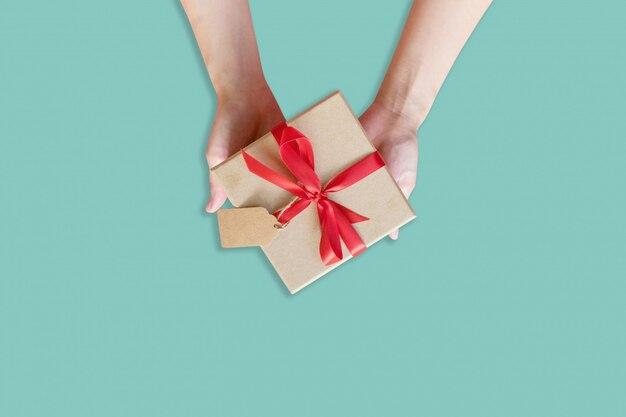 Draufsichthandfrau, die braune geschenkbox für neues jahr auf grünem pastellhintergrund hält