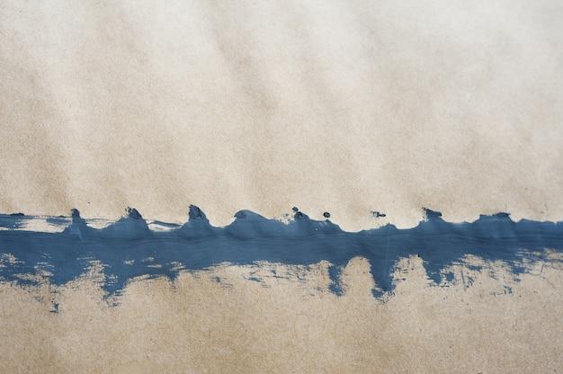 Draufsichthintergrund der grauen farbe auf kraftpapier mit tropfen