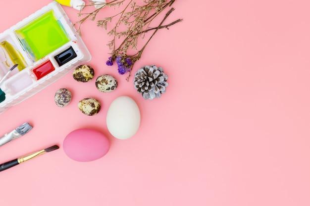 Draufsichthintergrund und farbensatz, der für ostern auf rosa hintergrund, ostereier sich vorbereitet