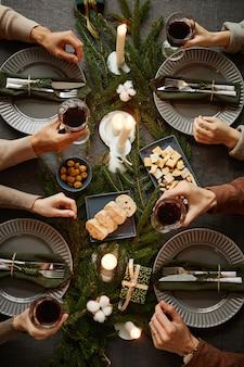 Draufsichthintergrund von vier leuten, die zusammen weihnachtsessen genießen, während sie von elegantem din...