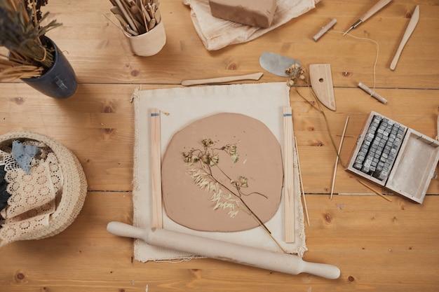 Draufsichthintergrundbild von roher pflanzenaufdruckkeramik auf holztisch mit werkzeugen in der töpferwerkstatt, kopierraum