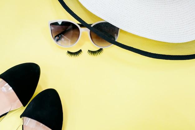 Draufsichthut und -sonnenbrille auf gelbem hintergrund mit sonnenlicht und schatten von kokosnussblättern.