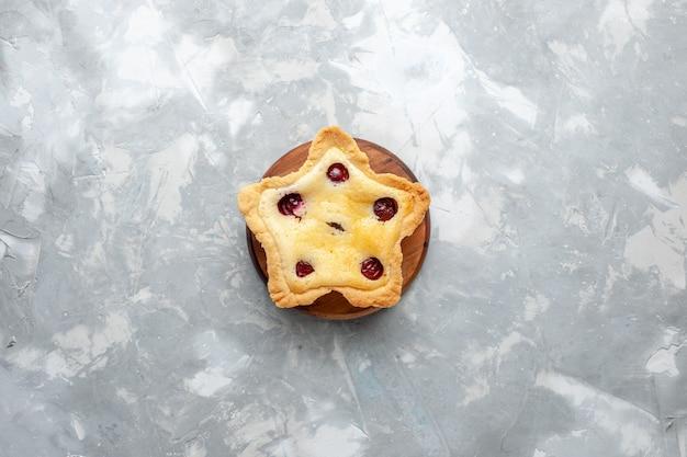 Draufsichtiger sternförmiger kuchen mit kirschen innen auf dem grauen schreibtischkuchenkeks süßer zuckerfarbfoto