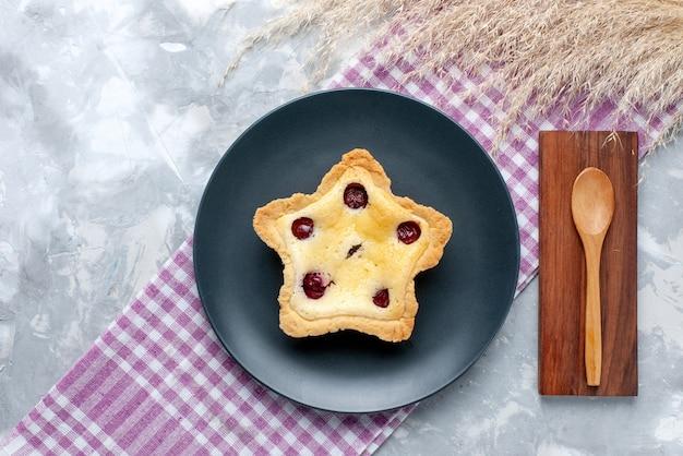 Draufsichtiger sternförmiger kuchen mit kirschen innen auf dem süßen zuckertee-auflaufkuchen des hellen tischkuchens