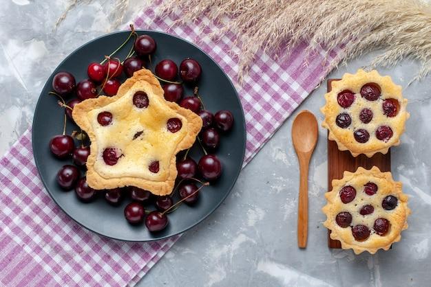 Draufsichtiger sternförmiger kuchen zusammen mit kirschkuchen und frischen sauerkirschen auf dem hellen schreibtischfruchtfrischkuchenkuchen