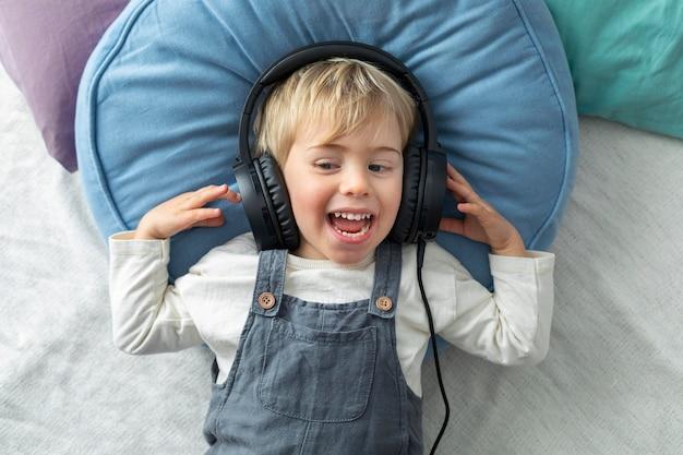 Draufsichtjunge, der musik auf kopfhörern hört