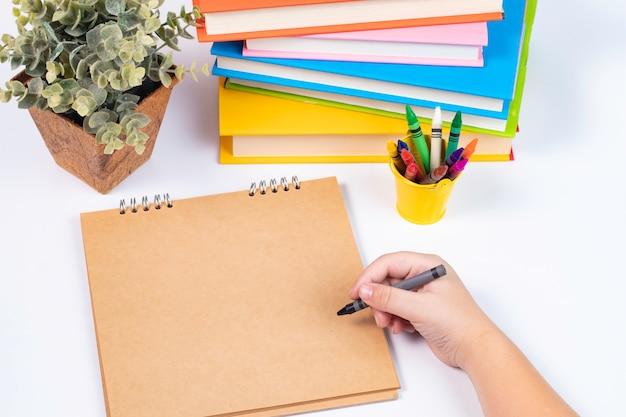 Draufsichtjungenhandzeichnung auf leerem sketchbook mit stapel büchern / zurück zu schule