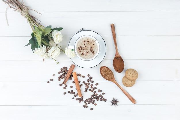 Draufsichtkaffee in der tasse mit gemahlenem kaffee, gewürzen, kaffeebohnen, keksen, blumen auf hölzernem hintergrund. horizontal