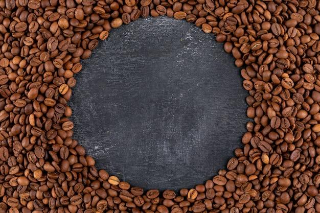 Draufsichtkaffeebohnen auf dunkler oberfläche