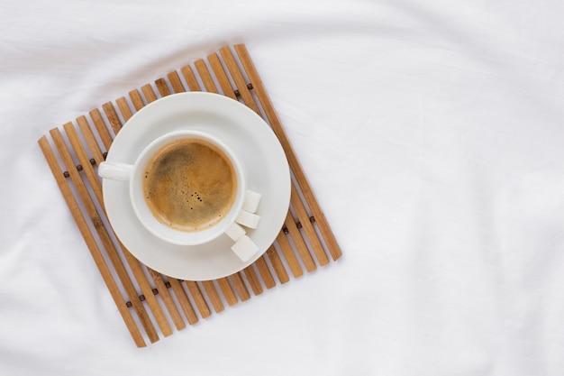 Draufsichtkaffeetasse auf einem weißen behälter