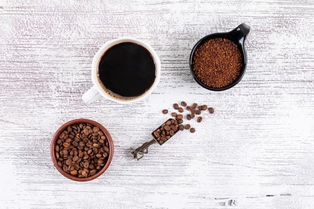 Draufsichtkaffeetasse mit kaffeebohnen und instantkaffee auf weißer tabelle