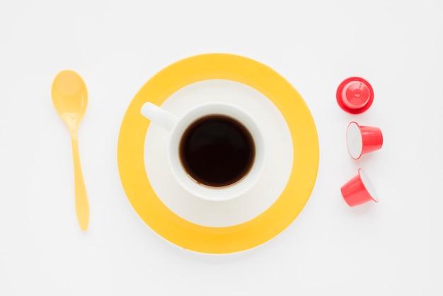 Draufsichtkaffeetasse mit löffel und kapseln
