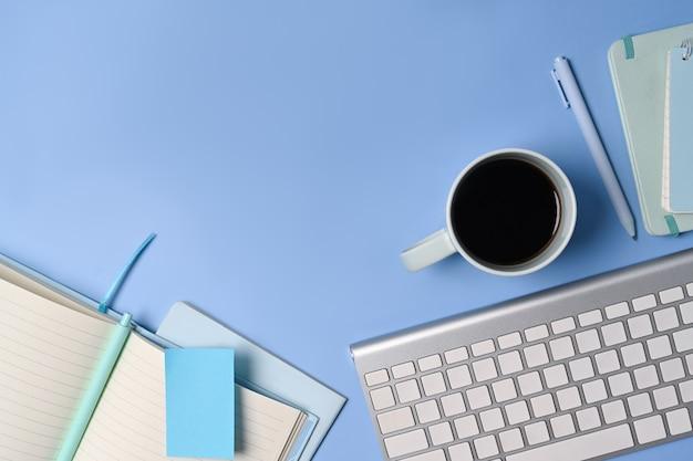 Draufsichtkaffeetasse, -tastatur und -notizbuch auf blauem hintergrund.