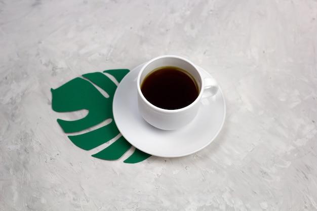 Draufsichtkaffeetasse und papiermonstera treiben auf einer steintabelle blätter
