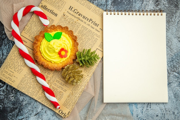Draufsichtkeks mit cremefarbenen weihnachtssüßigkeiten weihnachtsornamenten auf zeitungs-beige-schal ein notizbuch auf dunklem hintergrund