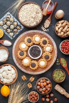 Draufsichtkekse mit schokolade und dunkler schokoladenschüssel auf holzbrett und anderen speisen zum frühstück auf dem tisch