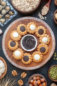 Draufsichtkekse mit schokolade und dunkler schokoladenschüssel auf holzbrett und anderen stoffen auf dem tisch
