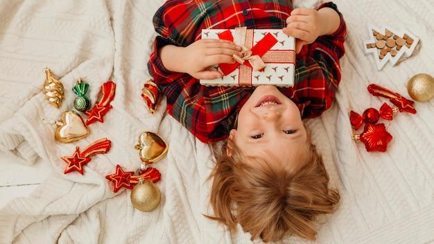 Draufsichtkind, das ein weihnachtsgeschenk im bett hält
