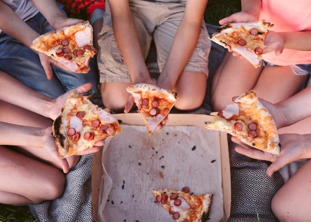 Draufsichtkinder, die eine scheibe pizza essen