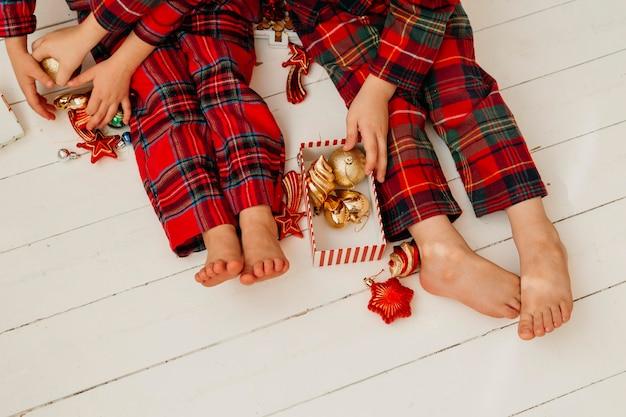 Draufsichtkinder in der weihnachtskleidung, die dekorationen hält
