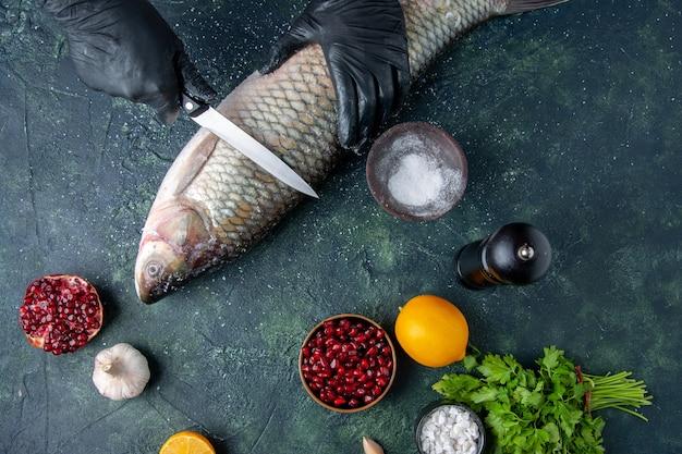 Draufsichtkoch mit handschuhen, die rohen fisch pfeffermühle granatapfelkerne in schüssel auf dem tisch schneiden