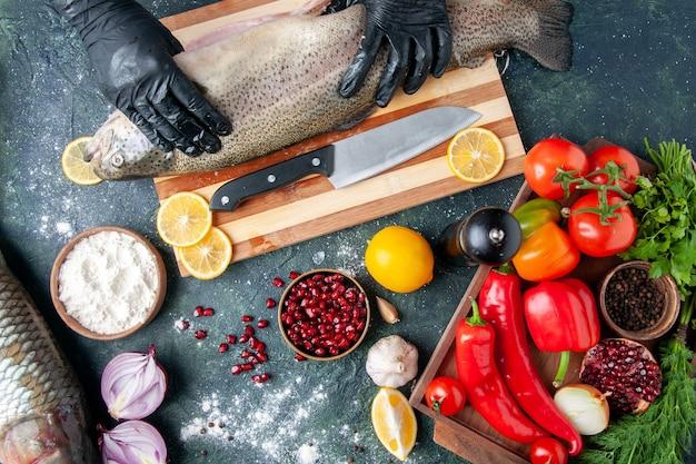 Draufsichtkoch mit schwarzen handschuhen, die rohen fisch auf holzbrett halten pfeffermühle mehlschüssel granatapfelkerne in schüssel auf dem tisch