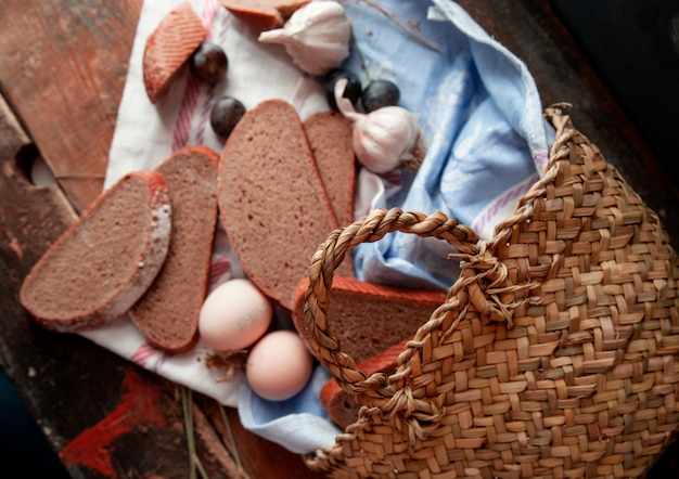 Draufsichtkorb mit brot schneidet eier, pflaume und knoblauch herum auf einem holztisch.