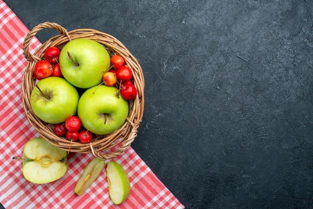 Draufsichtkorb mit fruchtäpfeln und süßkirschen auf dunkelgrauem hintergrundfruchtbeerenzusammensetzungsfrische-baumpflanze