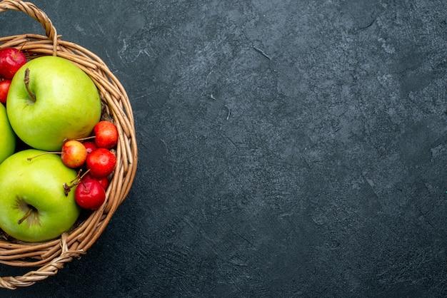 Draufsichtkorb mit fruchtäpfeln und süßkirschen auf frische-beeren-zusammensetzungsfrische des dunklen hintergrunds