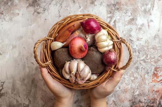 Draufsichtkorb mit gemüse, knoblauch, zwiebeln und rüben auf heller fotofarbe reife salatdiät
