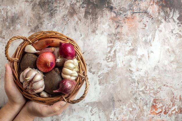 Draufsichtkorb mit gemüse-knoblauch-zwiebeln und -rüben auf heller fotofarbe reifer salatdiät freier raum